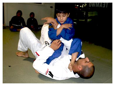 Kid Power student in a Brazilian Jiu Jitsu exercise with instructor
